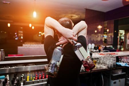 De jonge flessen van de barmanholding voor coctail bij de bar