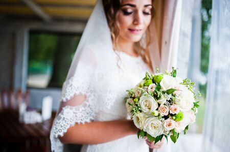 looked: Charming bride looked at wedding bouquet at her hands