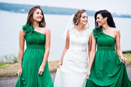 Bride with two bridesmaids on green dress