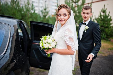 Bräutigam und Braut in der Nähe von Hochzeitsauto