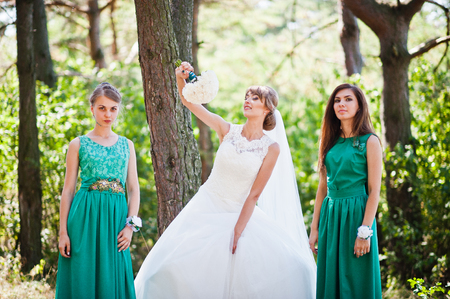 velvet dress: Cute bride with two bridesmaids on velvet green dress