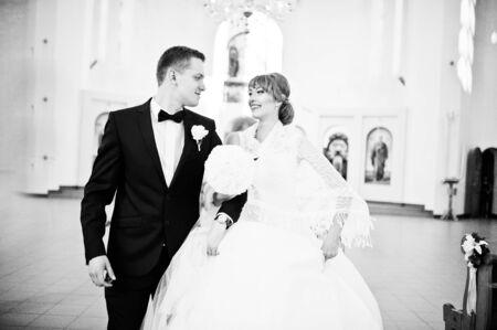 adentro y afuera: Pares de la boda feliz y sonri� en salir de la iglesia Foto de archivo