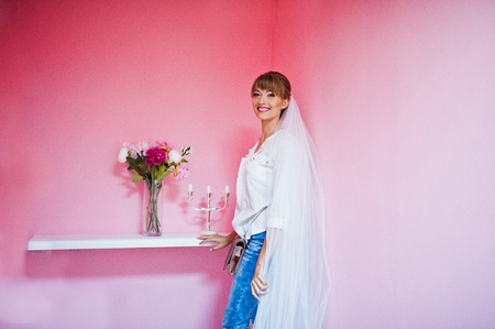 smiled: Smiled young girl bride at veil background pink wall with windowsill flowers and candlestick