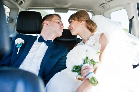back seat: Wedding couple in the back seat of car