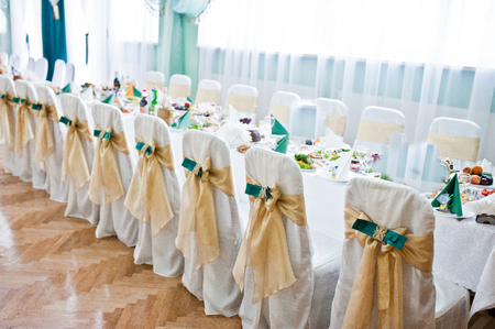 gold table cloth: Decorated wedding chairs with golden and green velvet ribbons Stock Photo