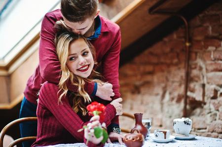 지붕에 큰 창문이있는 빈티지 카페에서 사랑 이야기에 빨간 드레스에서 젊은 아름 다운 세련된 부부, 소년은 여자 친구를위한 선물로 꽃을 제공합니다