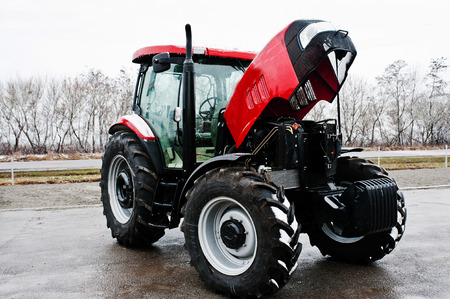 traction engine: New red tractor with open motor at snowy weather
