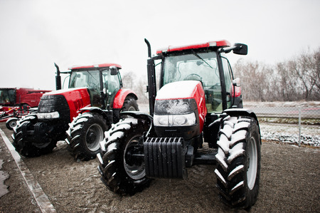 traction engine: Two new red tractor stay at snowy weather background combine Stock Photo