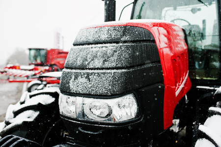 traction engine: Close up in front of the new red tractor at snowy weather