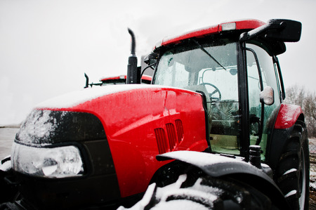 weather front: Close up in front of the new red tractor at snowy weather