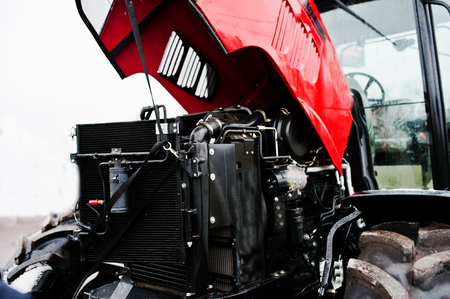traction engine: Close up in front of the new red tractor with open motor Stock Photo