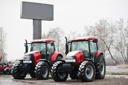 traction engine: Two new red tractor stay at snowy weather