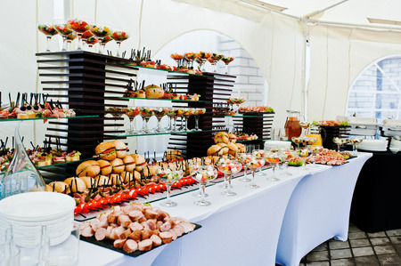 Buffet table of reception with burgers, cold snacks, meat and salads Stock Photo