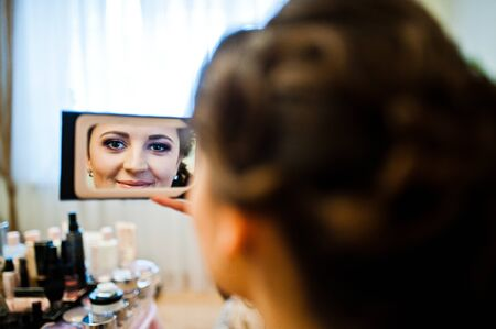 looked: Young pretty bride looked at the cosmetics mirror