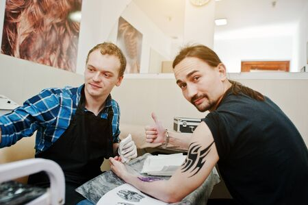master: Tattoo master make tattoo for rocker man at tattoo salon