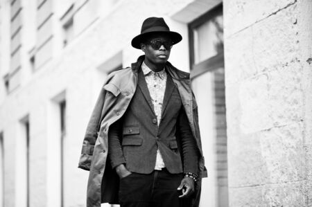 many windows: Fashion portrait of black african american man on green velvet jacket, black hat and coat cloak on his shoulders walking on streets of city background house with many windows. B&W photo