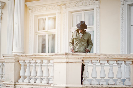 stay in the green: Fashion portrait of black african american man on green coat cloak and black hat, stay on the balcony of yellow mansion