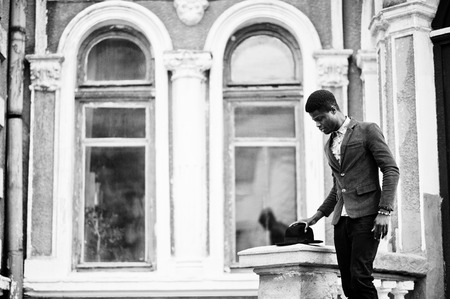 stay in the green: Fashion portrait of black african american man on green velvet jacket stay on stairs and wear his black hat background old mansion. B&W photo Stock Photo