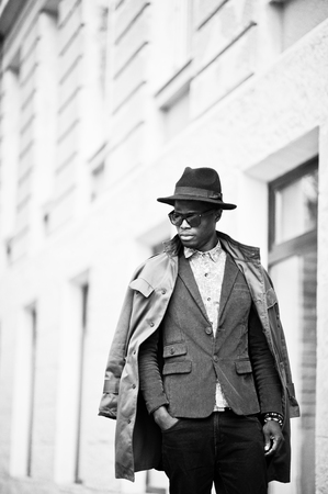 many windows: Fashion portrait of black african american man on green velvet jacket, black hat and coat cloak on his shoulders walking on streets of city background house with many windows. Vertical B&W photo Stock Photo