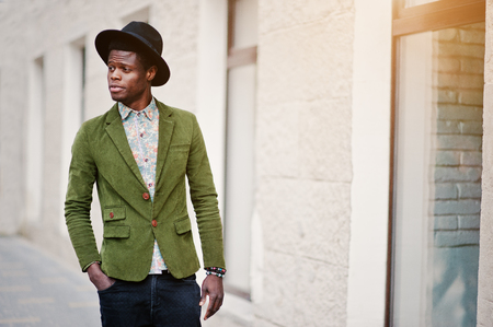 many windows: Close up fashion portrait of black african american man on green velvet jacket and black hat walking on streets of city background house with many windows