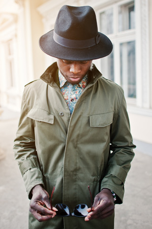 stay in the green: Close up fashion portrait of black african american man on green coat cloak and black hat with sunglasses stay background yellow mansion. Vertical photo Stock Photo