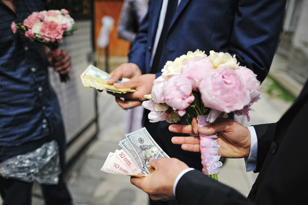 redemption: Wedding bouquet of peony at hands of groom with moneys. Redemption of bride on wedding