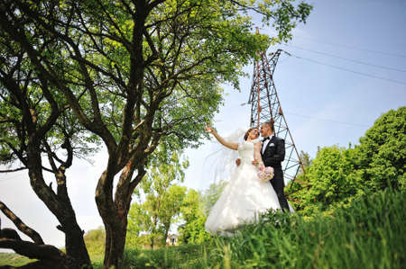 electrical tower: Fashionable happy wedding couple background electrical tower looking each other