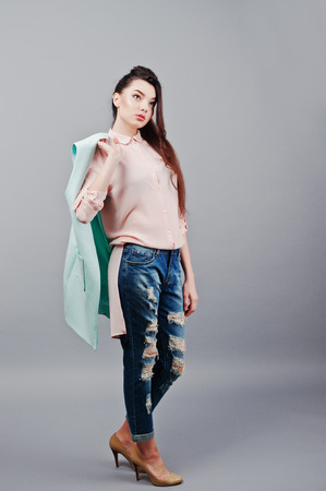 full shot: Full-length portrait young brunette girl wearing in pink blouse, turquoise jacket, ripped jeans and cream shoes .Fashion studio shot