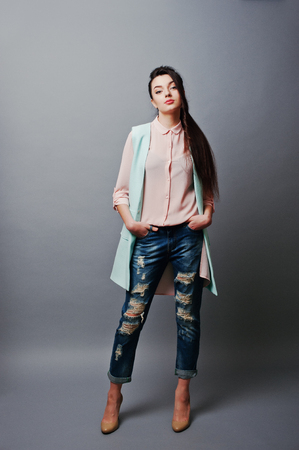 shot: Full-length portrait young brunette girl wearing in pink blouse, turquoise jacket, ripped jeans and cream shoes .Fashion studio shot