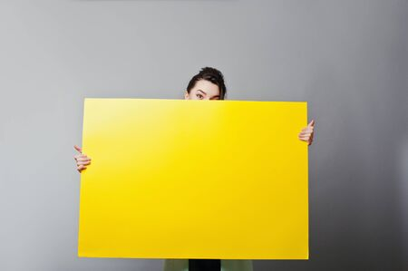 over the edge: Banner sign woman peeking over edge of blank empty yellow paper billboard with copy space for text. Beautiful caucasian woman looking surprised and funny.
