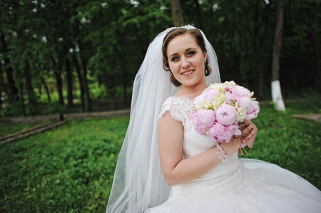 arm bouquet: Close up portrait of beautiful bride with peonies wedding bouquet in hands