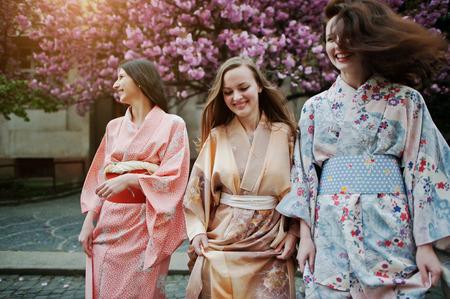 Three european girls wearing traditional japanese kimono background blossom pink sakura tree Foto de archivo