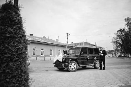 maffia: Stylish groom near maffia car at wedding cortege Stock Photo