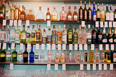 ajenjo: KYIV, UKRAINE - MARCH 25, 2016: Various alcoholic beverages bottles in the bar on the shelf. Editorial