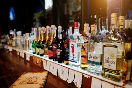 KYIV, UKRAINE - MARCH 25, 2016: Various alcoholic beverages bottles in the bar. Beefeater London dry gin in the center. Redakční