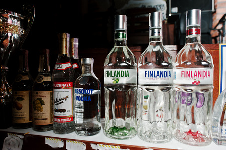 alcoholic beverages: KYIV, UKRAINE - MARCH 25, 2016: Various alcoholic beverages bottles in the bar. Finlandia Finland vodka at center Editorial