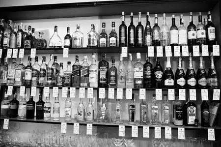 KYIV, UKRAINE - MARCH 25, 2016: Various alcoholic beverages bottles in the bar on the shelf. Redakční