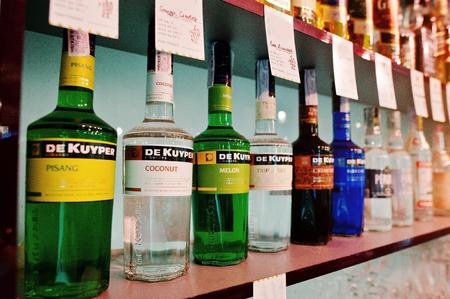 liqueurs: KYIV, UKRAINE - MARCH 25, 2016: Various alcoholic beverages bottles in the bar. Set of De Kuyper liqueurs Editorial