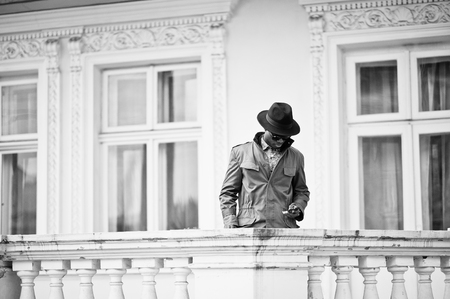 stay in the green: Fashion portrait of black african american man on green coat cloak and black hat, stay on the balcony of yellow mansion. B&W photo