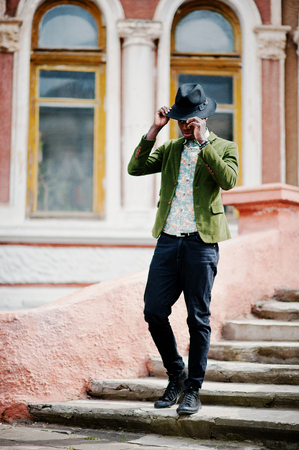 stay in the green: Fashion portrait of black african american man on green velvet jacket and black hat stay on stairs background old mansion. Vertical photo