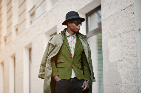 many windows: Fashion portrait of black african american man on green velvet jacket, black hat and coat cloak on his shoulders walking on streets of city background house with many windows Stock Photo