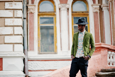 stay in the green: Fashion portrait of black african american man on green velvet jacket and black hat stay on stairs background old mansion.