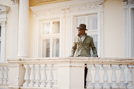stay in green: Fashion portrait of black african american man on green coat cloak and black hat, stay on the balcony of yellow mansion