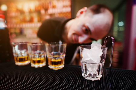 ice tongs: Glass with ice and tongs with three whiskey glasses background funny barman Stock Photo