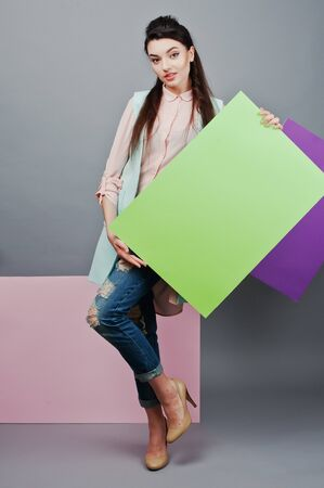 full shot: Full length of beautiful girl, with green blank advertising board , over gray background and pink and violet banner . Your text here. Concept art Stock Photo