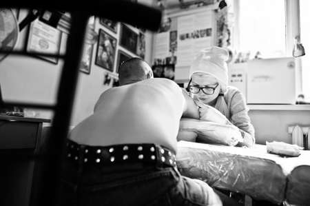 female likeness: Young blonde woman master tattooist in glasses and hat with tattoo machine at hands make tattoo Dreamcatcher at hand of man. Black and white photo