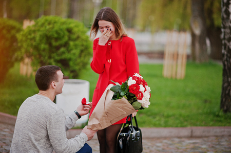 Marriage proposal. Man with boquet of flowers kneeling and give engagement ring for his girlfriend Foto de archivo
