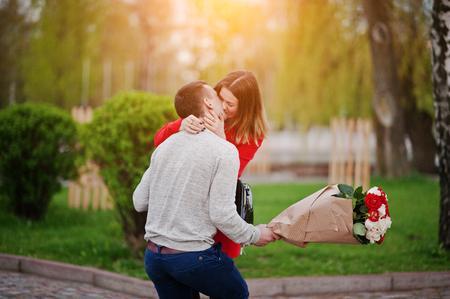 Huwelijksaanzoek. Kuste meisje en haar vriend met een boeket bloemen Stockfoto