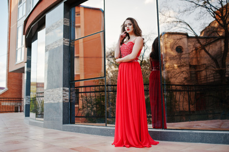red evening: Portrait of fashionable girl at red evening dress posed background mirror window of modern building