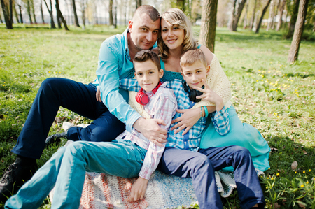 turqoise: Happy pregnant family with two sons, dressed in a turquoise clothes sitting on grass with flowers at park